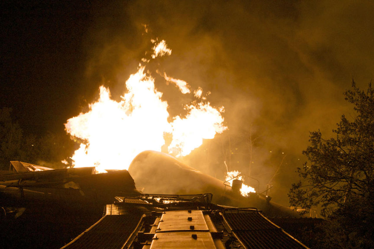 Flames rise from a derailed freight train early Wednesday July 11, 2012 in Columbus Ohio. Part of a freight train derailed and caught fire in Ohio's capital city early Wednesday, shooting flames skyward into the darkness and prompting the evacuation of a mile-wide area as firefighters and hazardous materials crews worked to determine what was burning and contain the blaze.(AP Photo/Chris Mumma)