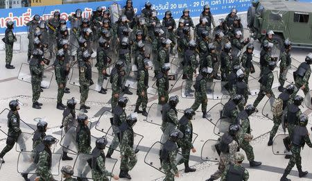 Soldiers hold their shields as they prepare to leave after guarding a shopping district to stop protests against military rule in central Bangkok