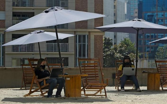 Parasols and deck chairs bring a beach feel to a coworking space on Sao Paulo's Paulista Avenue (AFP/Miguel SCHINCARIOL)
