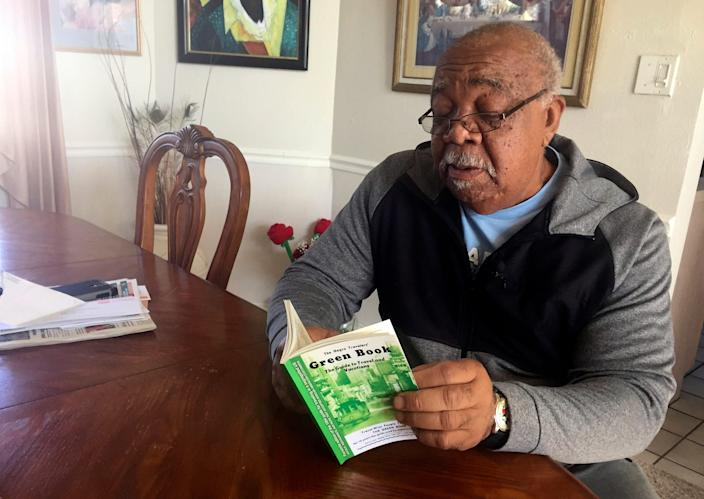"""In this Jan. 31, 2019 photo, Charles Becknell, Sr., 77, holds a copy of the 1954 edition of """"The Negro Motorist Green Book"""" at his home in Rio Rancho, New Mexico."""