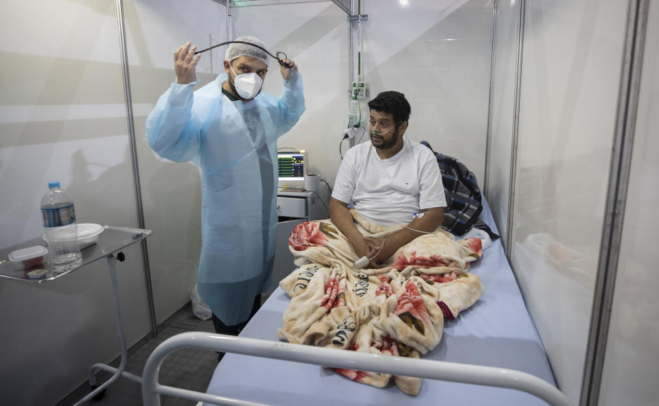 Doctor Malek Imad treats 34-year-old COVID-19 patient Everton Barbosa Godoy at the emergency unit of a field hospital in Ribeirao Pires, greater Sao Paulo area, Brazil, Tuesday, April 13, 2021. (AP Photo/Andre Penner)