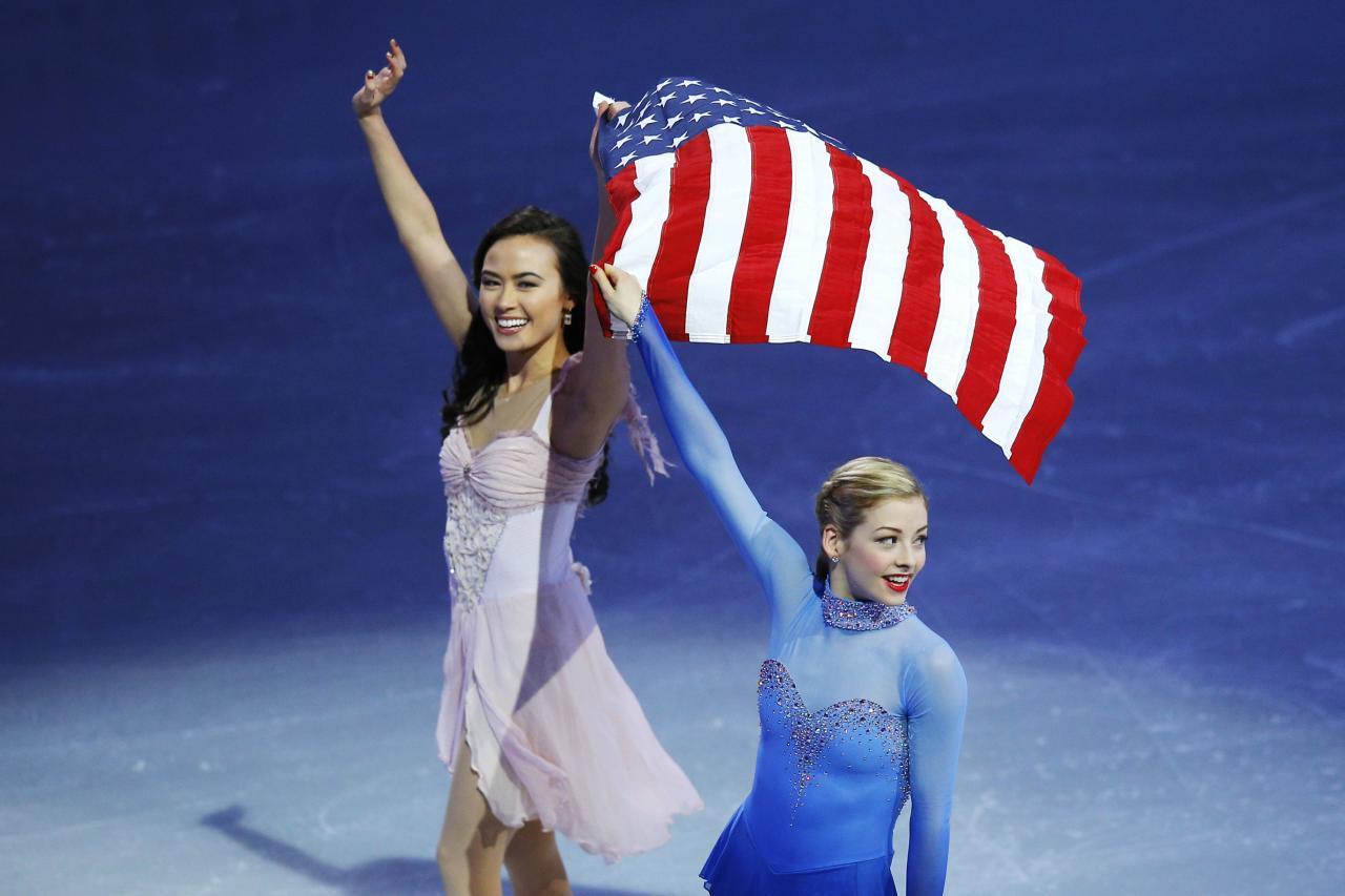 Team USA's Olympic figure skating team members Madison Chock and Gracie Gold (R) wave to the crowd at an exhibition event at the conclusion of the U.S. Figure Skating Championships in Boston, Massachusetts January 12, 2014. REUTERS/Brian Snyder (UNITED STATES - Tags: SPORT FIGURE SKATING)