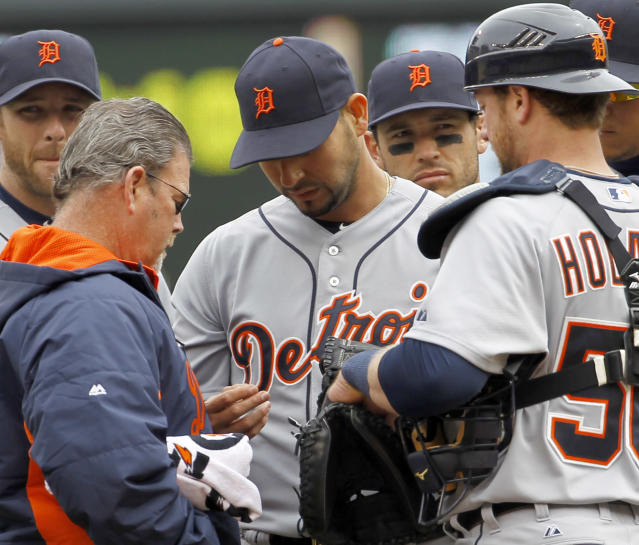 A trainer checks the hand of Detroit Tigers starting pitcher Anibal Sanchez, center, during the third inning of a baseball game against the Minnesota Twins in Minneapolis, Saturday, April 26, 2014. Sanchez left the game with a blister. (AP Photo/Ann Heisenfelt)