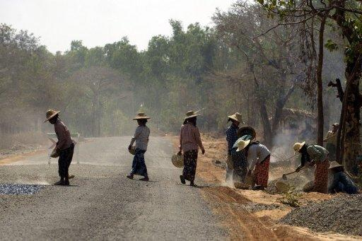Local women are seen repairing a damaged portion of a road between Myanmar's northern city of Bagan and Mandalay, on February 26. Western countries have begun to ease sanctions on Myanmar in response to the the recent promising steps and they are expected to further relax restrictions if April's polls are free and fair