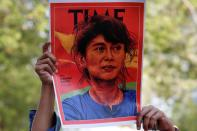 A person holds up a placard depicting Aung San Suu Kyi in Bangkok