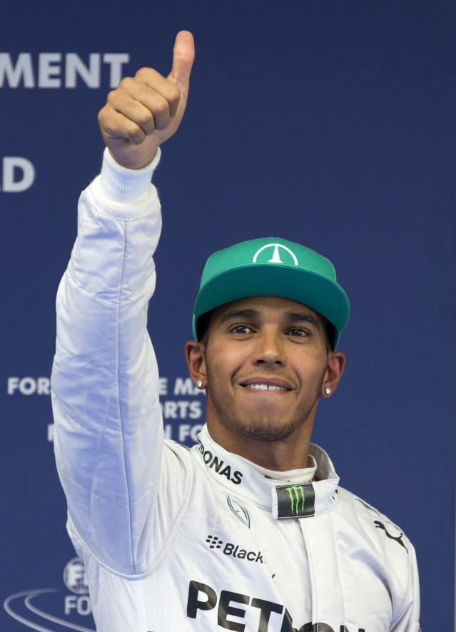 Mercedes driver Lewis Hamilton of Britain gestures to his fans after he won the pole position for Sunday's Chinese Formula One Grand Prix at Shanghai International Circuit in Shanghai, China Saturday, April 19, 2014. (AP Photo/Andy Wong)