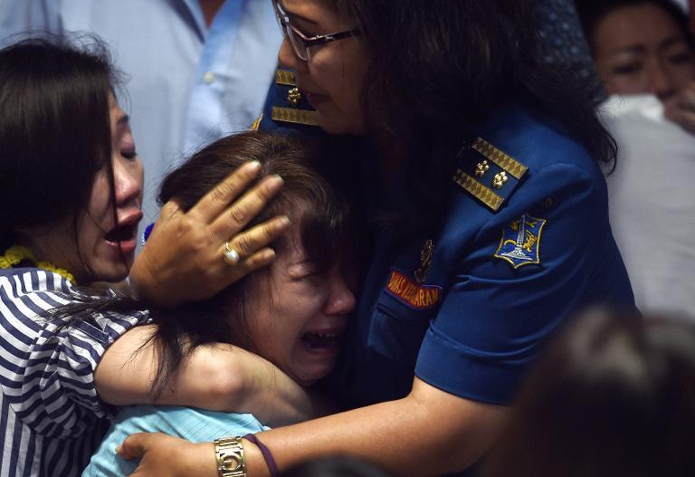 Family members of passengers onboard AirAsia flight QZ8501 react after watching news reports showing an unidentified body floating in the Java sea, inside the crisis-centre set up at Juanda International Airport in Surabaya