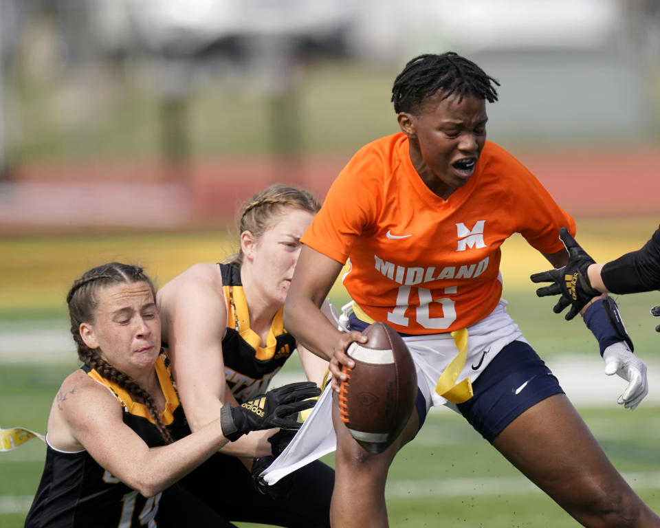 Midland quarterback E'leseana Patterson (16) is tackled by Ottawa defenders Jeffifer Anthony, left, and Courtney Wille during an NAIA flag football game in Ottawa, Kan., Friday, March 26, 2021. The National Association of Intercollegiate Athletics introduced women's flag football as an emerging sport this spring. (AP Photo/Orlin Wagner)