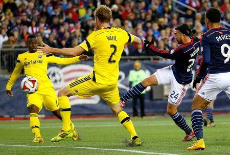 Nov 9, 2014; Foxborough, MA, USA; New England Revolution midfielder/forward Lee Nguyen (24) shoots a goal between Columbus Crew defender Tyson Wahl (2) and defender Waylon Francis (14) during the first half at Gillette Stadium. Mandatory Credit: Winslow Townson-USA TODAY Sports