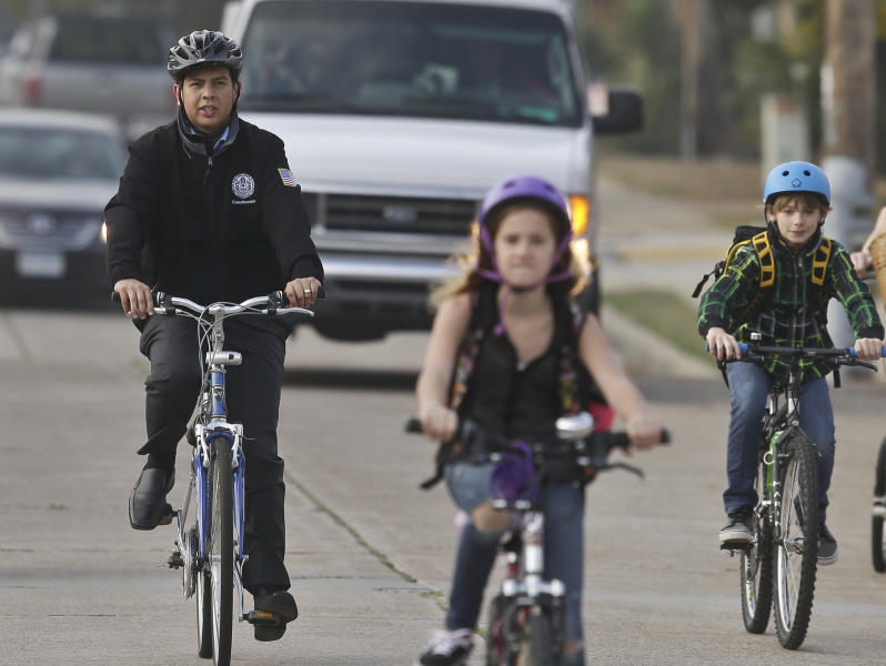 In a Thursday, Jan. 30, 2014 photo, San Diego Mayoral candidate David Alvarez, right, rides through traffic with children and parents headed to school, in San Diego. Alvarez finished second in a first round of voting by winning south of the freeway in predominantly Latino areas. Republican Councilman Kevin Faulconer easily topped a field of 11 candidates in a first round of voting by dominating in wealthier neighborhoods north of the freeway. (AP Photo/Lenny Ignelzi)