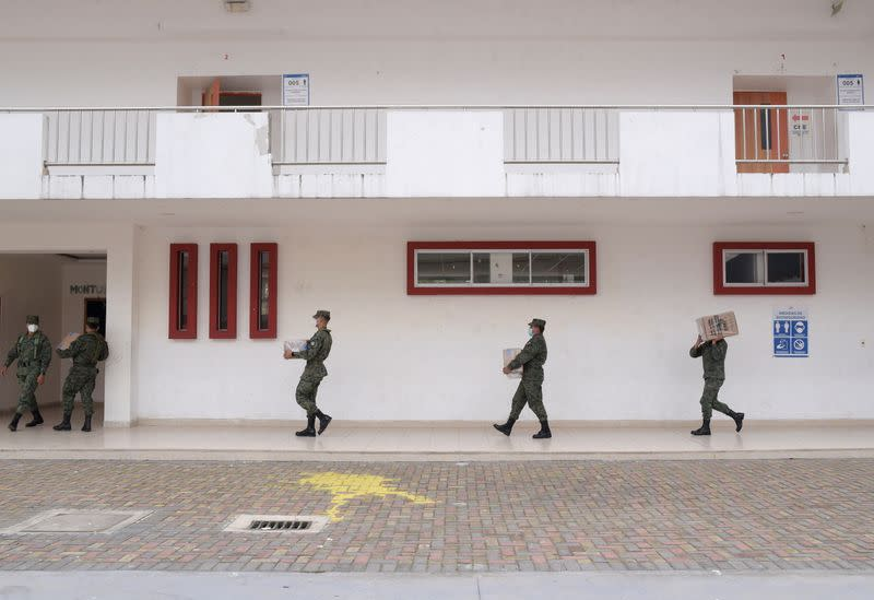 Soldiers carry electoral material at a polling station ahead of Ecuador's presidential election on February 7, in Quito