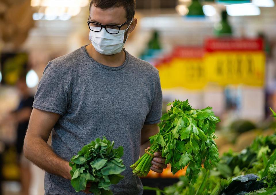 male wears medical mask against coronavirus while grocery shopping in supermarket or store