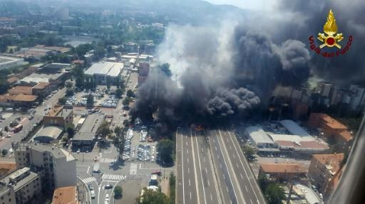 This handout picture taken from an helicopter and released by the Vigili del Fuoco, the Italian firement, on August 6, 2018, shows black smoke rising in the sky after a tanker exploded on the motorway close to the airport, in Bologna