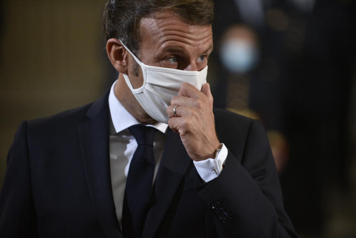 French President Emmanuel Macron adjusts his mask during a ceremony to celebrate the 150th anniversary of the proclamation of the Republic, at the Pantheon monument, Friday Sept.4. 2020 in Paris. (Julien de Rosa, Pool via AP)