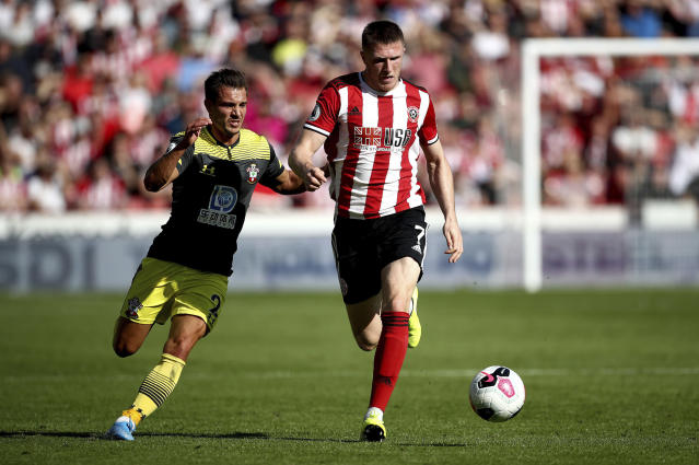 Southampton's Cedric Soares, left, and Sheffield United's John Lundstram battle for the ball during their English Premier League soccer match at Bramall Lane, Sheffield, England, Saturday, Sept. 14, 2019. (Tim Goode/PA via AP)