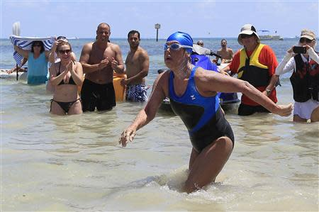 U.S. long-distance swimmer Diana Nyad , 64, walks to dry sand, completing her swim from Cuba as she arrives in Key West, Florida, September 2, 2013. REUTERS/Andrew Innerarity