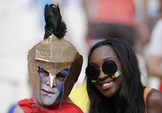 A Greece and an Ivory Coast supporter pose for a photograph prior to the group C World Cup soccer match between Greece and Ivory Coast at the Arena Castelao in Fortaleza, Brazil, Tuesday, June 24, 2014. (AP Photo/Fernando Llano)