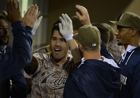 Mar 30, 2014; San Diego, CA, USA; San Diego Padres pinch hitter Seth Smith (12) celebrates with teammates in the dugout following a solo home run in the eighth inning on the opening day baseball game against the Los Angeles Dodgers at Petco Park. Christopher Hanewinckel-USA TODAY Sports