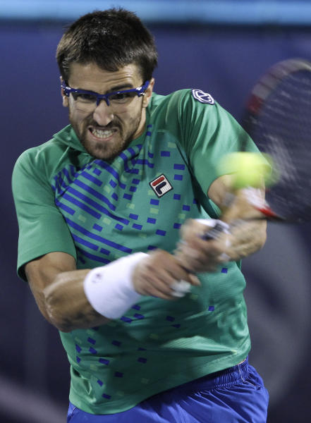Janko Tipsarevic of Serbia returns the ball to Novak Djokovic of Serbia during a quarterfinal of the Emirates Dubai ATP Tennis Championships in Dubai, United Arab Emirates, Thursday, March 1, 2012. (AP Photo/Hassan Ammar)