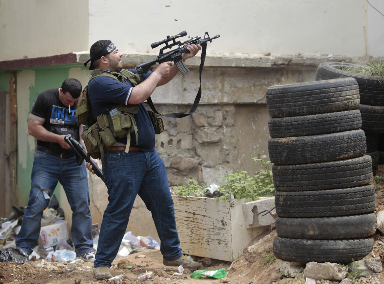 A Sunni gunman fires during a clashes, in the northern port city of Tripoli, Lebanon, Sunday May 13, 2012. Gunfire broke out in the city Saturday and continued through the night primarily between a neighborhood populated by Sunni Muslims who hate Syrian President Bashar Assad and another area with many Assad backers from his Alawite sect. Lebanon's national news agency NNA said one soldier was shot dead by a sniper in the city early Sunday. Another man was found dead on the side of a road while a third died after a shell landed in a residential neighborhood. (AP Photo/Hussein Malla)
