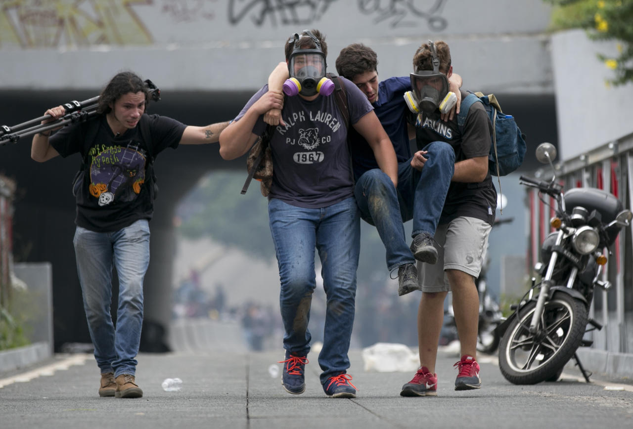 <p>Demonstrators carry a youth away from tear gas fired by police during an opposition demonstration in Caracas, June 7, 2016. Protesters attempted to march to demand thatgovernment pursue a recall referendum against President Nicolas Maduro. (AP/Ariana Cubillos) </p>
