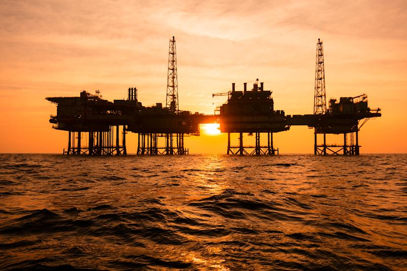 An offshore oil rig in silhouette at sunset