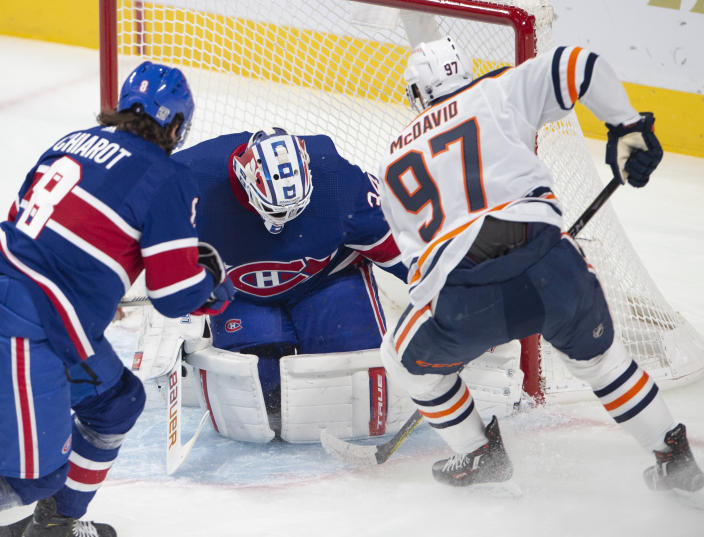 Montreal Canadiens goaltender Jake Allen (34) stops Edmonton Oilers center Connor McDavid (97) as Canadiens defenseman Ben Chiarot (8) moves in during first-period NHL hockey game action in Montreal, Thursday, Feb. 11, 2021. (Ryan Remiorz/The Canadian Press via AP)