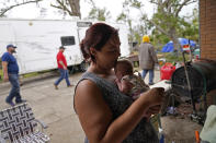 Hannah Bourque holds one of her two-week old twins outside the camper she is living in with her grandfather, while her mother lives in a tent in the backyard, outside their heavily damaged home in the aftermath of Hurricane Laura and Hurricane Delta, in Lake Charles, La., Friday, Dec. 4, 2020. (AP Photo/Gerald Herbert)