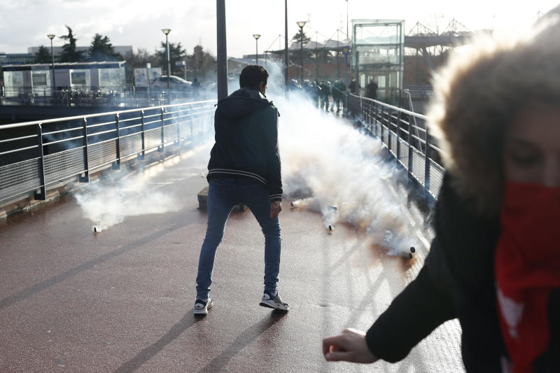 Riot police throw teargas canister during a demonstration of unionist and yellow vests, in Creteil, outside Paris, Wednesday, Jan. 9, 2019. About 200 protesters, including unionists and yellow vests, gathered Wednesday in Creteil, a Paris suburb, as Macron was doing a visit in a facility dedicated to handball. Some scuffles broke out with police forces that used tear gas to keep the crowd at a distance from the French leader. (AP Photo/Thibault Camus)