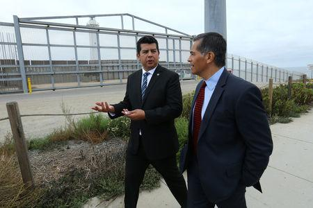 Attorney General of California Xavier Becerra accompanied by San Diego City Councilmember David Alvarez walks along the U.S.-Mexico border at the Pacific Ocean after announcing a lawsuit against the Trump Administration over its plans to begin construction of border wall in San Diego and Imperial Counties, in San Diego, California, U.S., September 20, 2017. REUTERS/Mike Blake