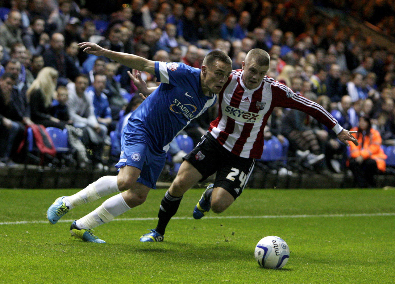 Brentford's Jake Bidwell (right) and Peterborough United's Paul Taylor battle for the ball during the Johnstone's Paint Trophy match at London Road, Peterborough.