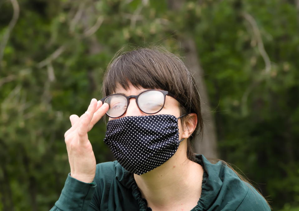 Headshot of Young Adult Brunette Woman Cleaning Fog (Condensed Water) of her Eyeglasses