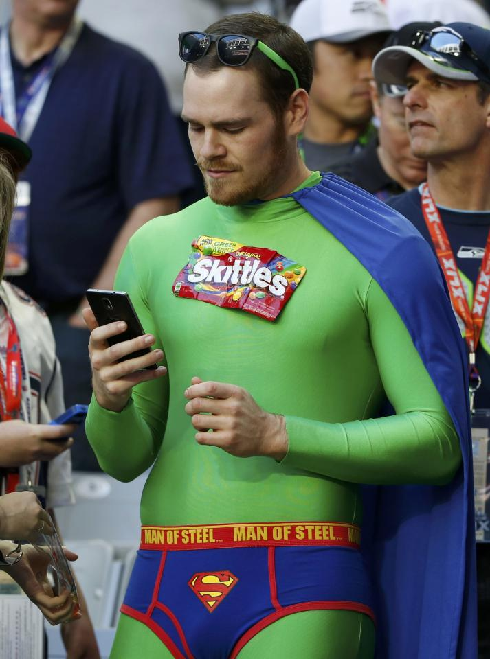 A Seattle Seahawks football fan checks his phone ahead of the start of the NFL Super Bowl XLIX football game against the New England Patriots in Glendale, Arizona, February 1, 2015. REUTERS/Lucy Nicholson (UNITED STATES  - Tags: SPORT FOOTBALL)