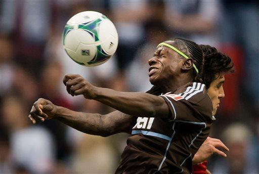 Vancouver Whitecaps' Darren Mattocks, left, of Jamaica, heads the ball away from FC Dallas' George John during the first half of an MLS soccer game in Vancouver, British Columbia on Saturday April 27, 2013. (AP Photo/The Canadian Press, Darryl Dyck)