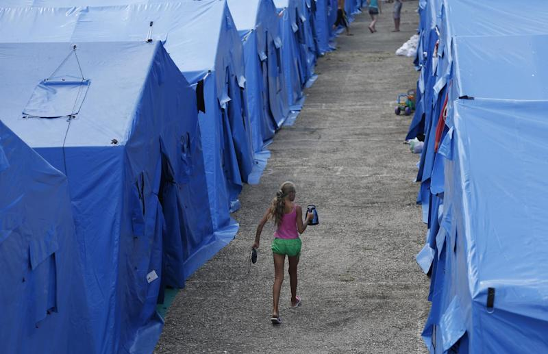 A girl carries a kettle at a temporary facility outside from the Crimean capital Simferopol, for refugees from eastern Ukraine, on July 17, 2014