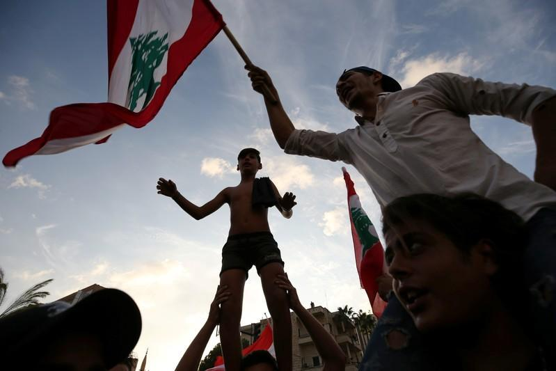 Demonstrators carry national flags during a protest targeting the government over an economic crisis in the port city of Sidon