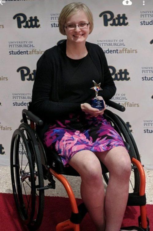 The author sitting in her wheelchair, smiling
