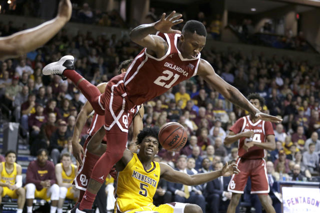 Oklahoma's Kristian Doolittle (21) loses his balance while defending against Minnesota's Marcus Carr (5) during the second half of an NCAA college basketball game in Sioux Falls, S.D., Saturday, Nov. 9, 2019. (AP Photo/Nati Harnik)