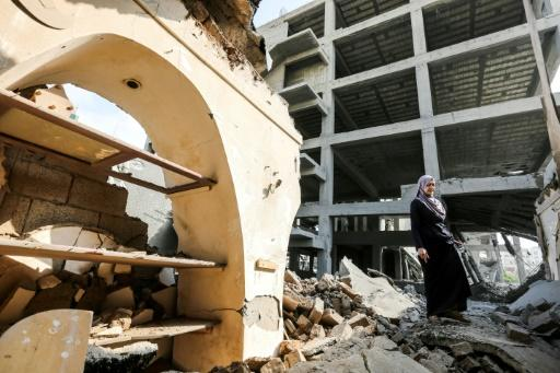 A Palestinian woman walks through rubble in the damaged Arts and Crafts Village in Gaza City on July 15, 2018, after the building next door was hit by Israeli air strikes the day before