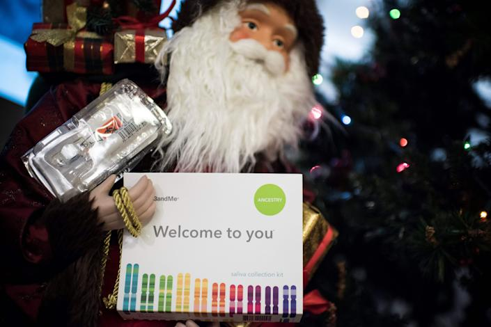 This illustration picture shows a saliva collection kit for DNA testing displayed in the arms of a Father Christmas doll in Washington, DC on December 19, 2018 as Americans are increasingly offering those tests to relatives during the Holiday season. - Between 2015 and 2018, sales of DNA test kits boomed in the United States and allowed websites to build a critical mass of DNA profiles. The four DNA websites that offer match services --  Ancestry, 23andMe, Family Tree DNA, My Heritage -- today have so many users that it is rare for someone not to find at least one distant relative. (Photo by Eric BARADAT / AFP)        (Photo credit should read ERIC BARADAT/AFP via Getty Images)