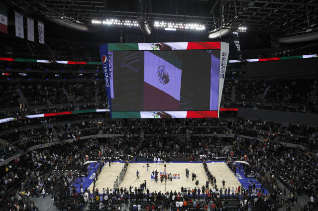 The San Antonio Spurs and the Phoenix Suns line up on the court during the singing of the Mexican national anthem prior their regular-season NBA basketball game in Mexico City, Saturday, Dec. 14, 2019. (AP Photo/Rebecca Blackwell)