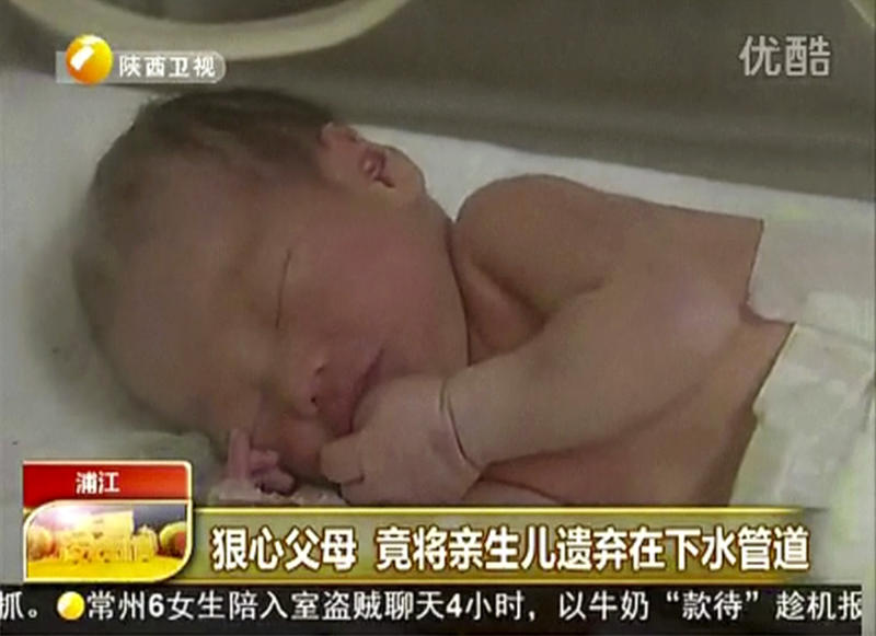 In this still image made from video from May 25, 2013, a baby who was rescued after being trapped in a sewage pipe just below a squat toilet in a public building, lies on a bed at a hospital in Jinhua city, eastern China. A 22-year-old single woman who alerted the authorities of a newborn boy trapped in a sewer in eastern China has admitted that she was the mother, but had refused to come forward because she could not support the child. (AP Photo/Shaanxi TV via AP Video)  CHINA OUT