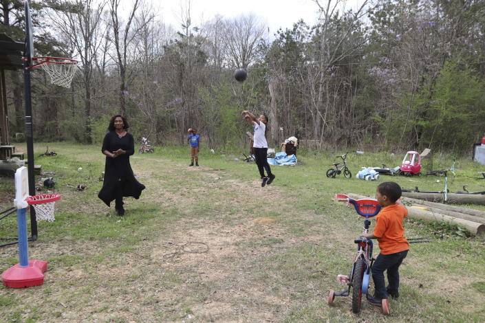 """Kendall Turner, 10, launches a basketball into a hoop outside his home in Fayette, Miss., while playing with his mother, Annie, and siblings on Monday, March 22, 2021. """"You got a lot of parents who are actually out there working to try to take care of home, and when it comes to food, you want to make sure that your family is eating well,"""" she said. """"Nobody wants to just be eating ramen noodles and hotdogs all day,"""" Annie Turner says. (AP Photo/Leah Willingham)"""