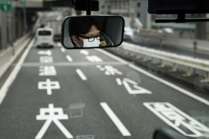 A bus driver is reflected in the mirror, Tuesday, July 13, 2021, in Tokyo. (AP Photo/Jae C. Hong)