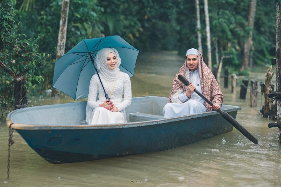 The bride and groom posing in a small boat. — Picture from Facebook/Meen Photographer