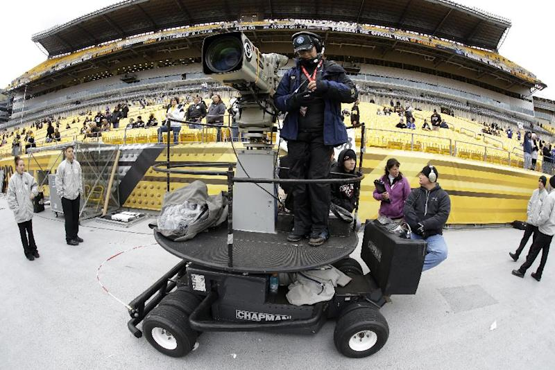FILE - In this Nov. 10, 2013, file phot, a CBS sideline camera operator prepares for an NFL football game between the Pittsburgh Steelers and the Buffalo Bills in Pittsburgh. The NFL says CBS will televise eight of its Thursday night games next season. The leagues says the contract is for one year, and they have an option to extend it for 2015. (AP Photo/Gene J. Puskar, File)