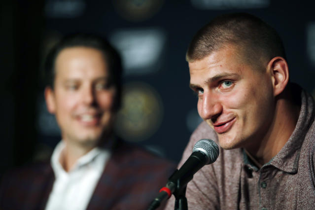 Denver Nuggets center Nikola Jokic, of Serbia, front, makes a point as Josh Kroenke, president and governor of the Denver Nuggets, looks on during a news conference to outline a contract extension for Jokic and the re-signing of guard Will Barton by the NBA basketball team Monday, July 9, 2018, in Denver. (AP Photo/David Zalubowski)