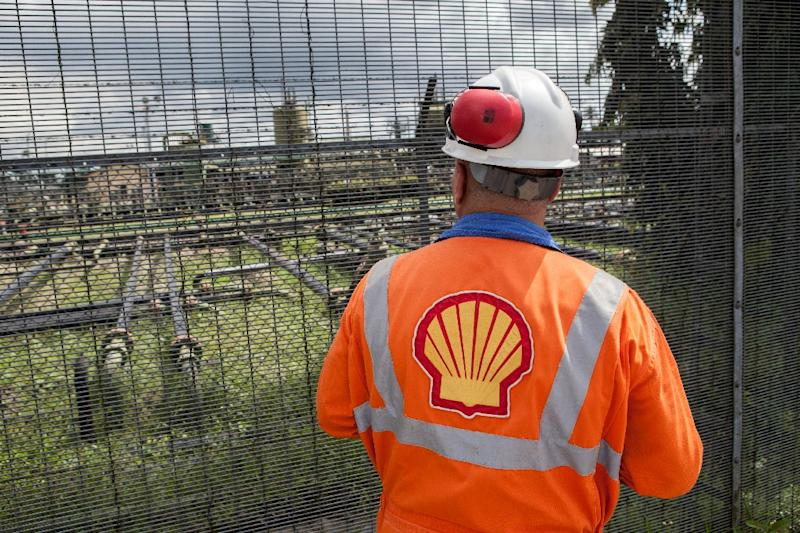 An employee at the Shell Agbada 2 flow station looks at the station from behind a gate in Port Harcourt, Nigeria on September 30, 2015