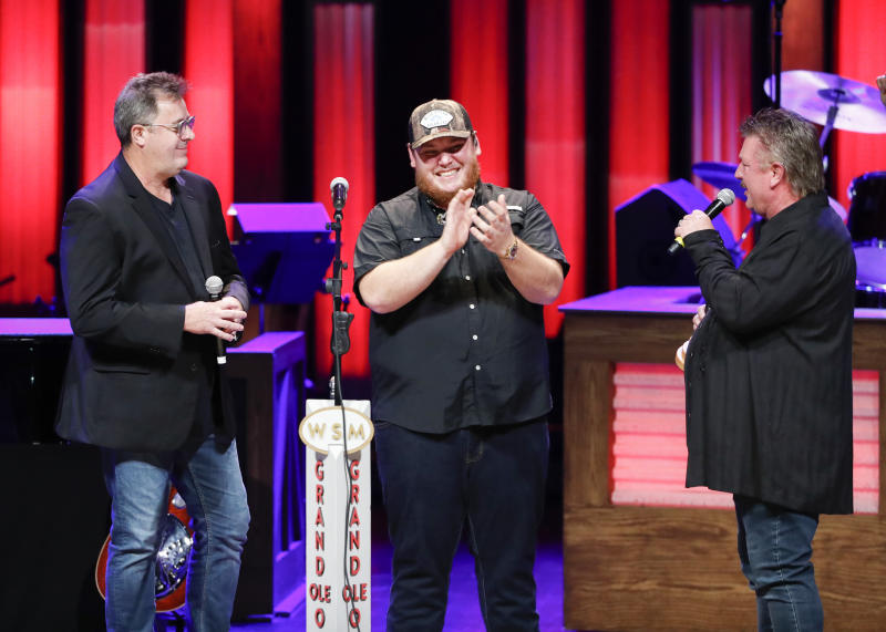 """Vince Gill, left, and Joe Diffie, right, welcome Luke Combs to the Grand Ole Opry at """"Luke Combs Joins the Grand Ole Opry Family,"""" Tuesday, July 16, 2019, in Nashville, Tenn. (Photo by Al Wagner/Invision/AP)"""