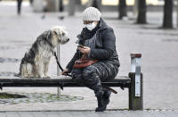 A woman with a face mask and a dog sit on a bench at the almost abandoned downtown in Duisburg, Germany, Monday, Jan. 25, 2021. (AP Photo/Martin Meissner)